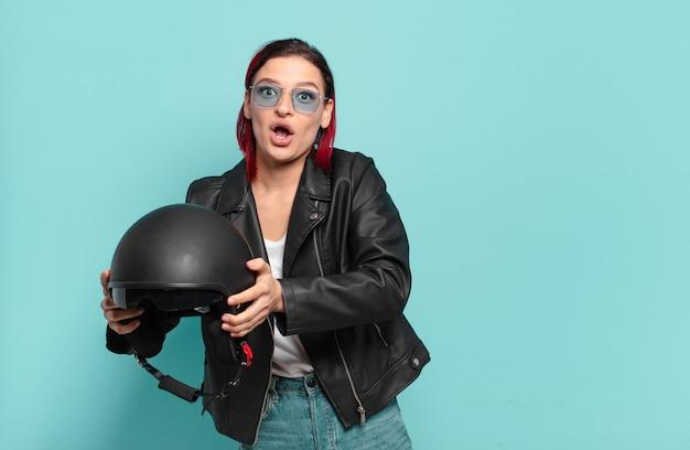 赤い髪のクールな女性のバイクライダーのコンセプト