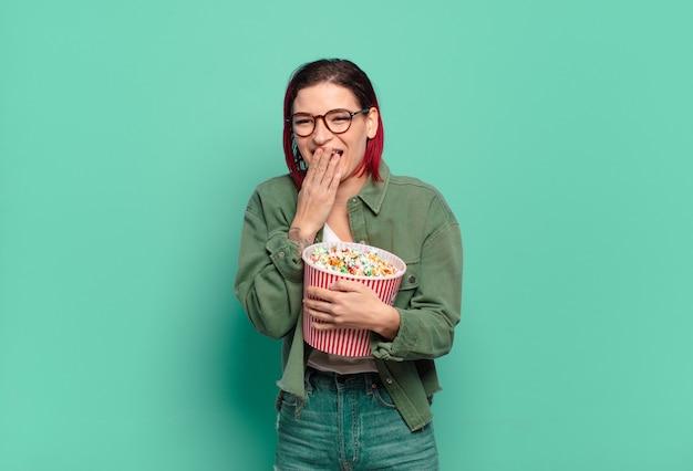 Рыжие волосы классная женщина с попкорном и пультом от телевизора