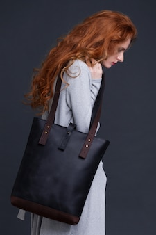 Red hair fashion model holding large dark blue leather bag on dark background. girl wearing long blue jumper.