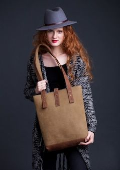 Red hair fashion model holding large leather bag on dark background. girl wearing jumper and hat.
