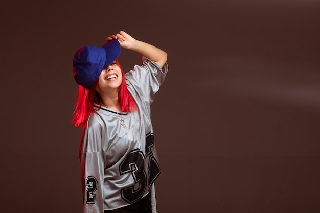 Девушка с красными волосами в спортивной одежде смотрится весело.
