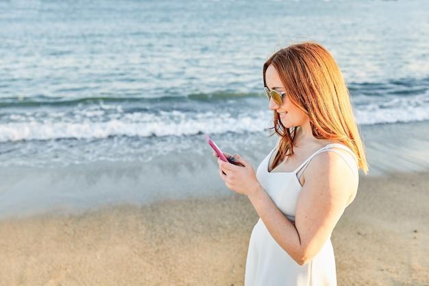 モバイルで話しているビーチの赤い髪の少女