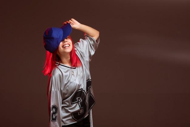 La ragazza dai capelli rossi in abiti sportivi sembra divertente.