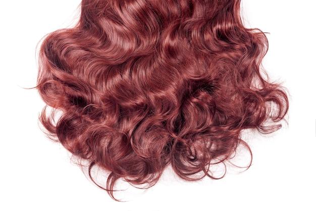 빨간 머리는 흰색 절연입니다. 물결 모양의 긴 곱슬 머리 가까이, 헤어 익스텐션, 재료 및 화장품, 헤어 케어, 가발. 헤어 스타일, 이발 또는 살롱에서 죽어가는, 긴 빨간 가발.