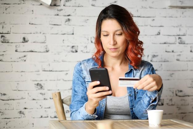 Латинская женщина с красными волосами, сидящая с телефоном и картой