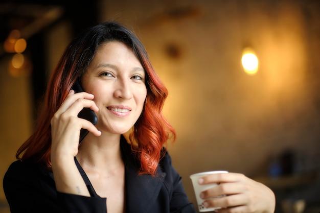 Женщина с рыжими волосами держит чашку во время звонка