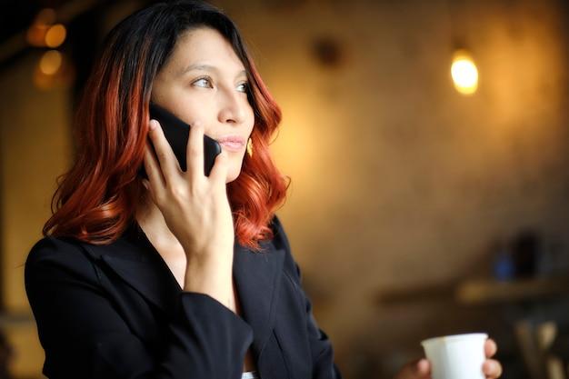 Женщина с рыжими волосами делает очень сосредоточенный звонок