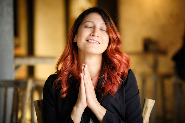 Женщина с красными волосами, сидящая в ресторане