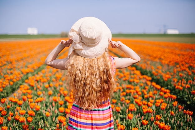 Red hair woman  standing by the back on tulip field