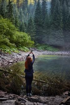山の湖の近くで彼女のスマートフォンを使用して写真を撮る赤毛の女性観光客。カルパティア山脈、ロソハン湖でのハイキング