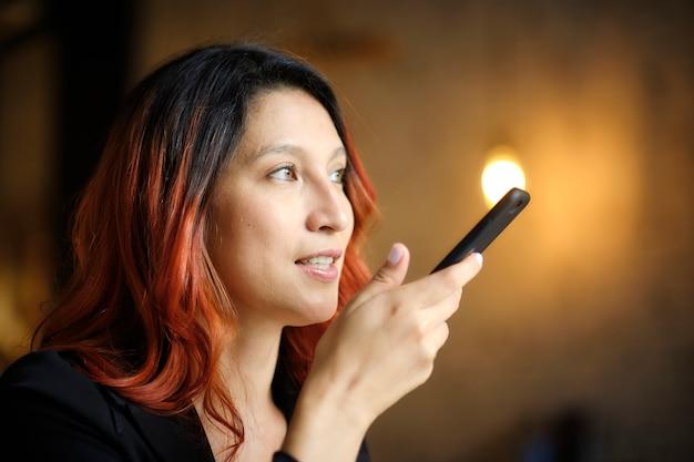 Рыжая женщина использует свой мобильный телефон