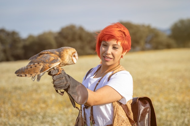 Red hair woman with a white owl on her arm