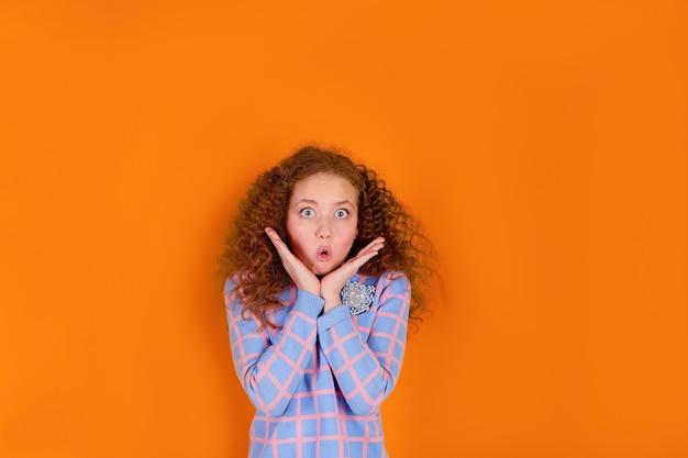オレンジ色の背景に赤い髪と巻き毛の女の子、驚いた