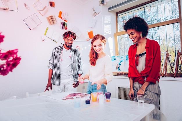 나가서는 예술가. 대리석 페인팅에서 마스터 클래스를 제공하는 재능있는 영감을받은 빨간 머리 예술가