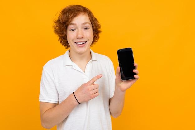 黄色の背景にモックアップと電話で白いtシャツを着た赤毛の魅力的なハンサムな男の子