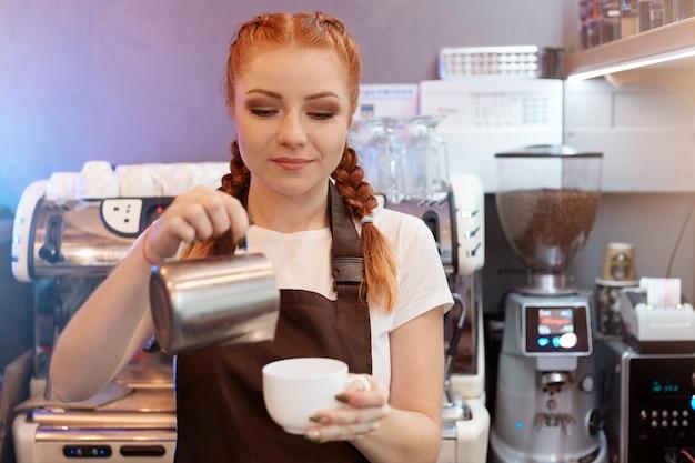 Рыжая девушка-бариста варит кофе из турка в кофейне