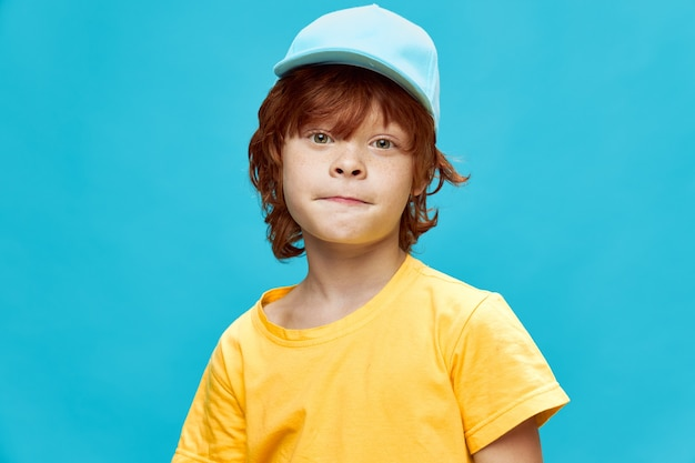Red-haired boy in a cap pursed his lips in a yellow t-shirt blue background