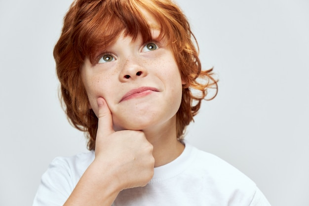 Red-haired boy holds his hand on his face and looks up smile white t-shirt