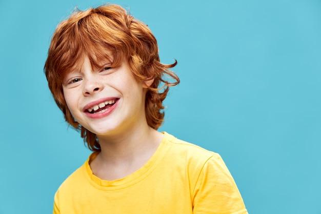 Рыжий мальчик смеется над изолированным в желтой футболке, склонившись в сторону
