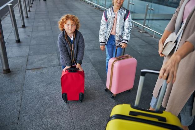 Рыжий мальчик, опираясь на красный чемодан