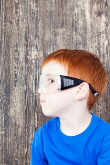투명 고글로 머리에 옷을 입고 빌더를 재생하는 동안 유럽 모양의 나가서는 소년