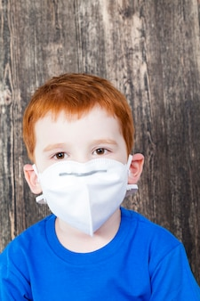 먼지로부터 보호하기 위해 마스크를 쓰고 빌더를 연주하는 동안 유럽인 외모의 나가서는 소년