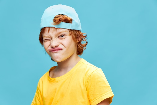 Red-haired boy with a cap on his head grimacing yellow t-shirt