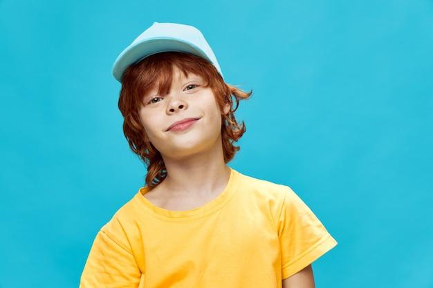 Red-haired boy with a cap on his head tilting his head to one side smile yellow t-shirt against blue isolated background