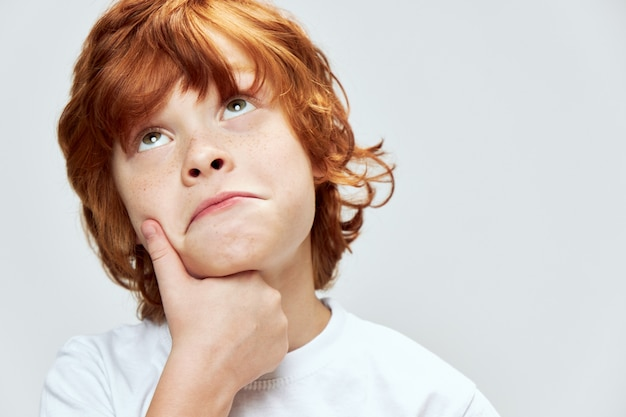 Red-haired boy with a sad expression looks up and holds his hand on his chin