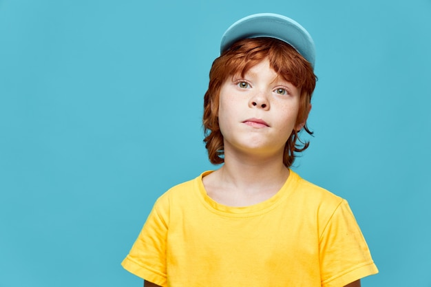Red-haired boy with a surprised expression on his face blue cap yellow t-shirt blue background cropped view