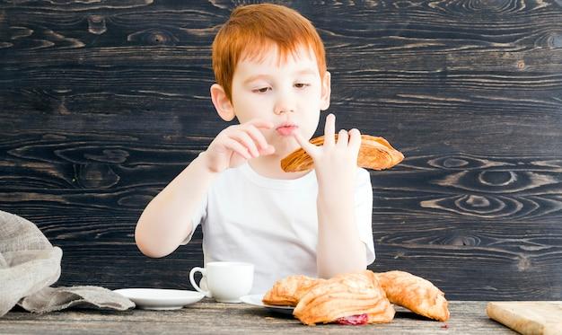 Рыжий мальчик со сладкими булочками с фруктовой красной начинкой, крупным планом работы на кухне