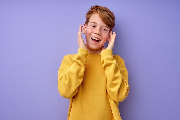 目を大きく開いた赤毛の少年はびっくり。真の人間の感情と反応。クレイジーな興奮した10代の少年が変な顔をして、口を大きく開けて感情的に身振りで示し、驚きを表現します