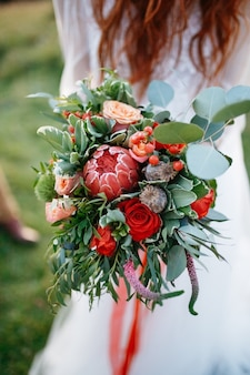 Red haired bride holds perfect wedding bouquet made of red