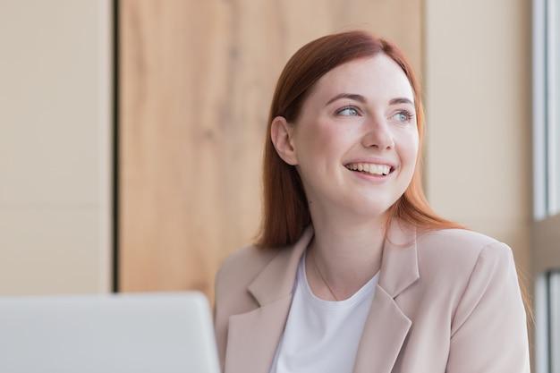 コンピューターに座って笑っている赤い髪のビジネス女性は満足のいく結果を得ました