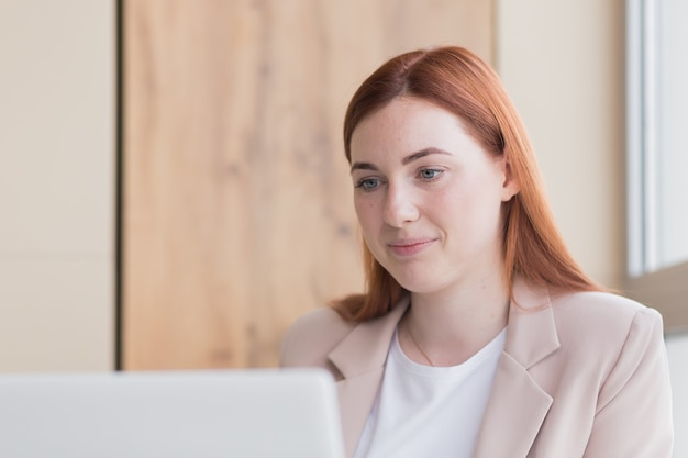 Red haired business woman smiling while sitting at a computer got a satisfactory result