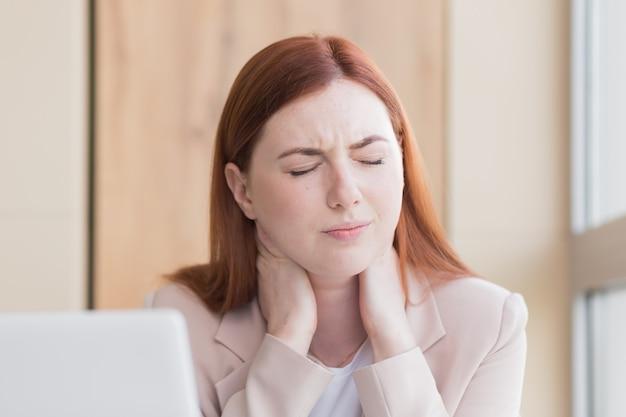 重度の歯痛とコンピューターの過労で頭痛を持つ赤い髪のビジネス女性
