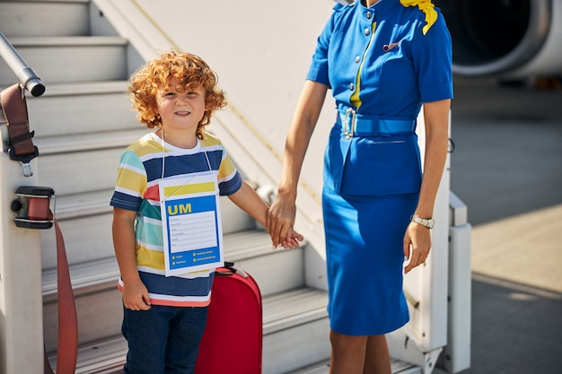 Red-haired child in a company of a flight attendant