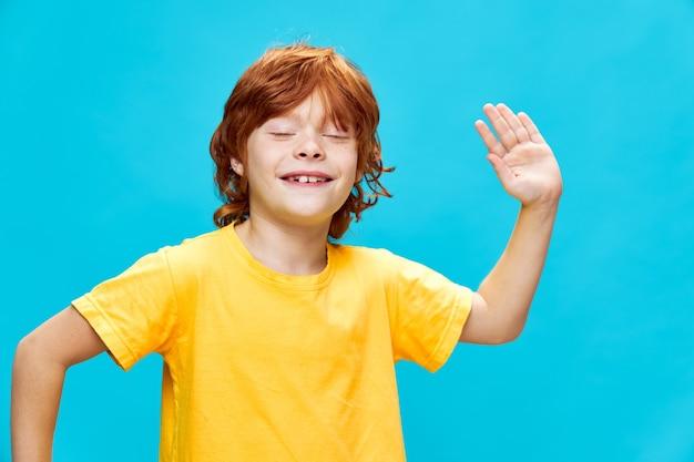 Рыжий ребенок с открытым ртом и веселым выражением лица танцует