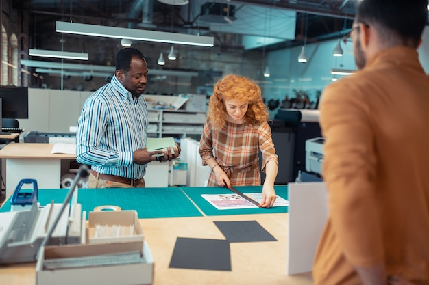 赤毛の同僚。新しいプロジェクトの浅黒い肌のリーダーの近くに立っている赤毛のインテリアデザイナー