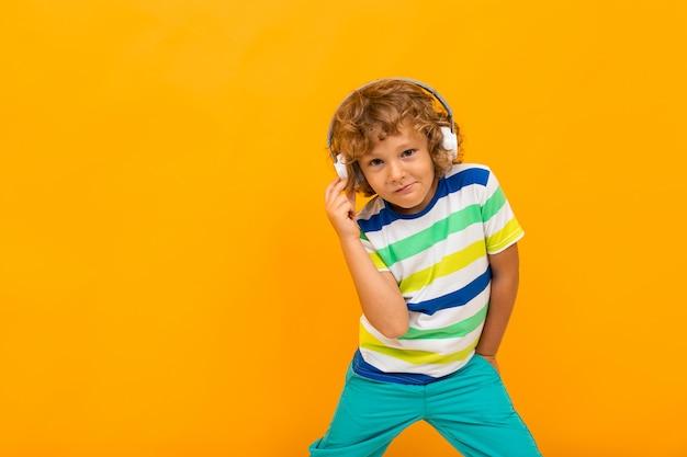 Рыжий кудрявый мальчик слушает музыку в больших наушниках на желтом фоне