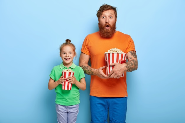 Red haired daughter and father eat popcorn