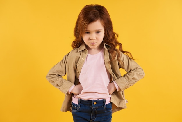Red-haired disgruntled girl folded arms in hips.