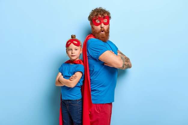 Red haired father and daughter play superhero game together, stand backs, have fun