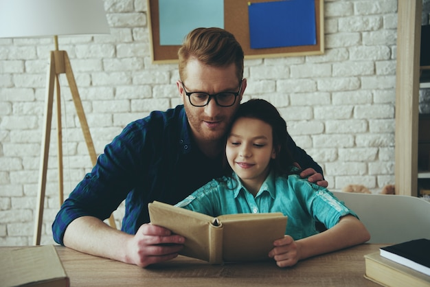 Red haired father in glasses reads fairy tale.