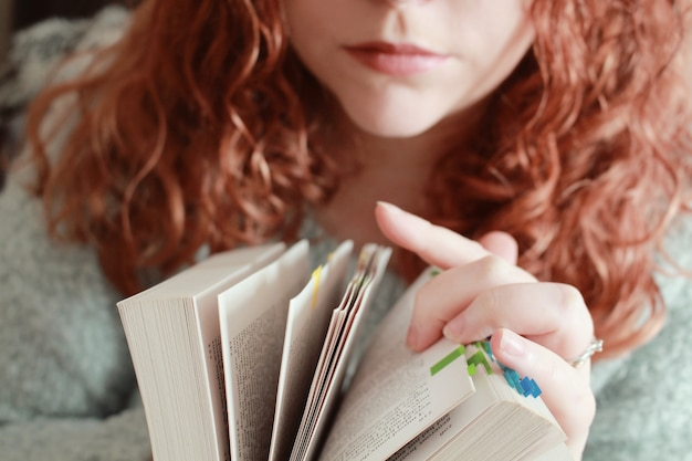 Red-haired female with a serious facial expression looking through a book