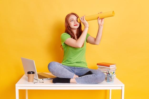Рыжие женщины в повседневной одежде сидят на столе со скрещенными ногами и делают подзорную трубу из бумаги
