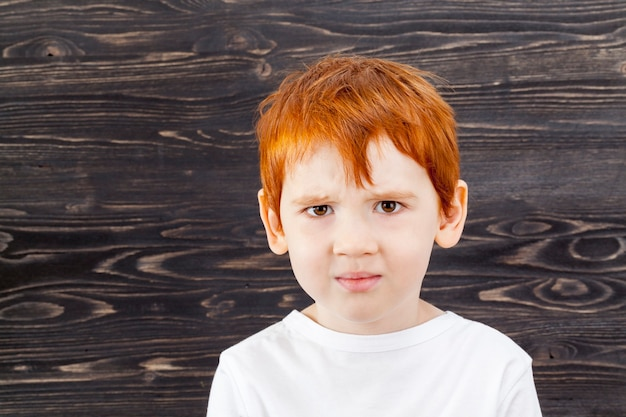 Red-haired five year old child with angry expression against wooden wall