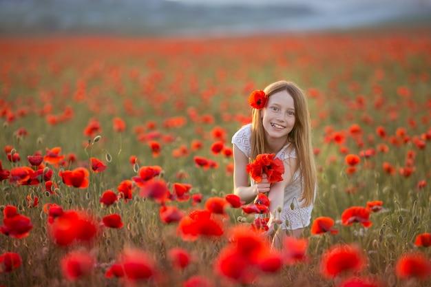 Рыжая девушка 12-13 лет с цветами в волосах на фоне сельскохозяйственного поля