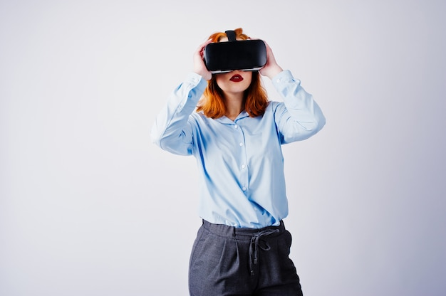 Red haired girl in blue blouse with vr glasses  isolated on white.