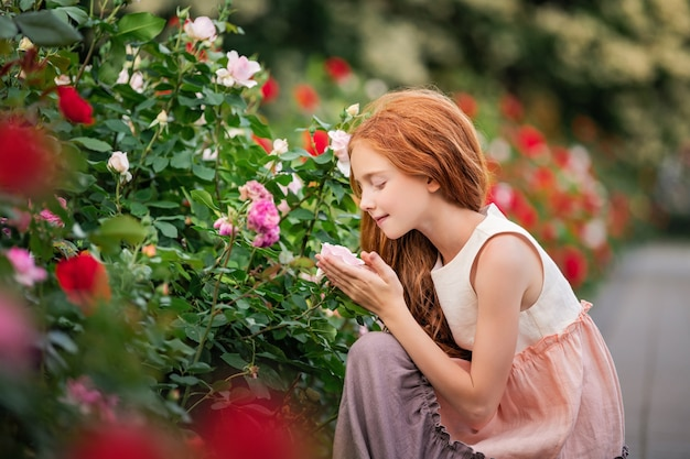夏に咲く庭でバラを嗅ぐ赤毛の女児
